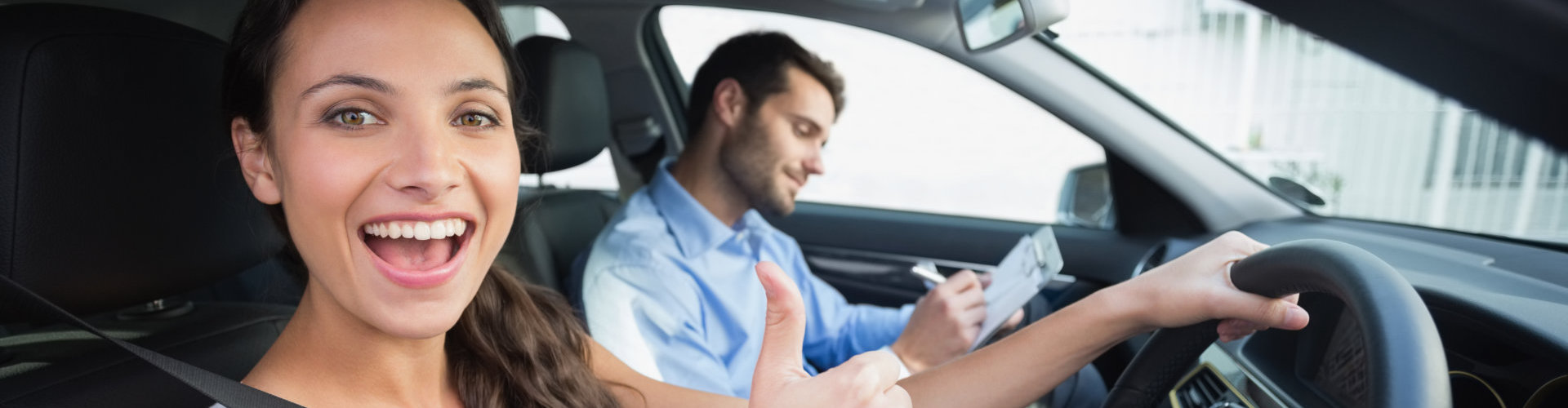girl raising her thumb while in a driving lesson